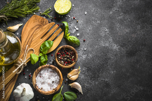 Fotobehang Aromatische Olive oil, herbs and spices on a dark stone table.
