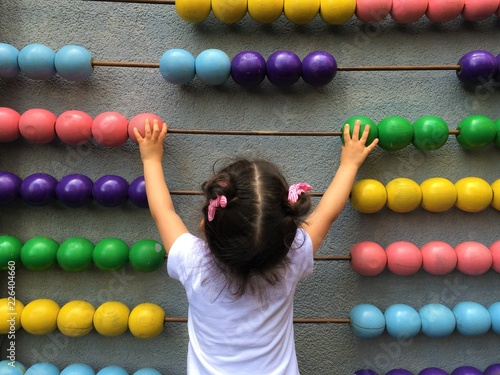 A cute girl playing with wooden abacus. Educational concept for kids. Learing to count. Math for children. Math for children.