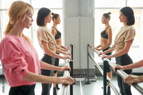 Photo  Row of elegant young women practicing ballet moves standing by bar against mirro