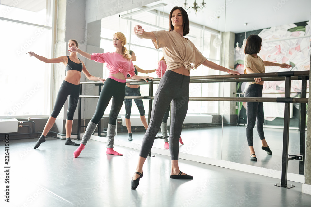 Photo  Full length portrait of three elegant young women practicing ballet moves standi