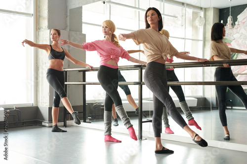 Full length portrait of row of elegant young women practicing ballet moves stand Canvas Print