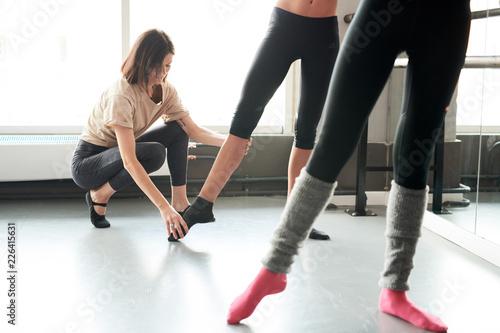 Photo  Full length portrait of female ballet teacher positioning feet of unrecognizable