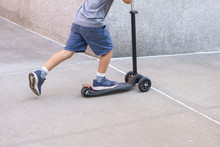 Young Boy In Shorts Riding A Micro Mini Scooter Down A City Sidewalk