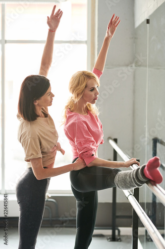 Side view portrait of female ballet teacher positioning student in dance class a Canvas Print