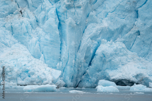 Close view of Holgate Glacier shows deep crevasses and icebergs with its teal blue color to the ice. Inside of Kenai Fjords National Park