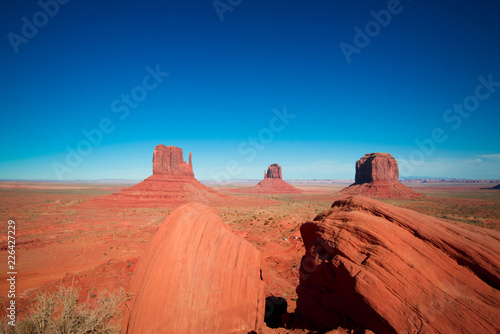 Foto op Canvas Baksteen sunset in the desert with scenic rocks and monument