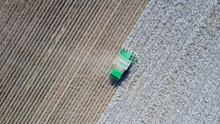 Aerial Image Of A Six Row Baler Cotton Picker Working In A Field.