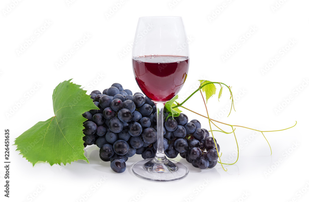 Glass of red wine against of blue grapes cluster