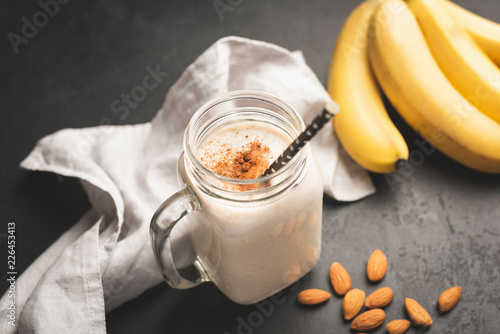 Photo Stands Milkshake Banana smoothie or protein shake in drinking jar topped with cinnamon. Toned image, selective focus