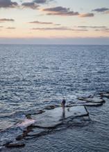 Fisherman Fishing In Sea During Sunset