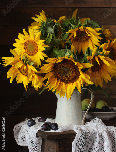 Still life with a bouquet of yellow sunflowers, plums and apples.