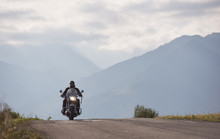 Bearded Motorcyclist In Sunglasses And Black Leather Clothing Riding Modern Powerful High-speed Motorbike Along Empty Road On Blue Foggy Mountains And Bright Cloudy Summer Sky Copy Space Background .
