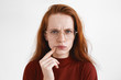 Picture of puzzled young red haired woman in spectacles frowning, having suspicious look, touching lips. Beauitful pensive ginger girl being frustrated with something. Human facial expressions
