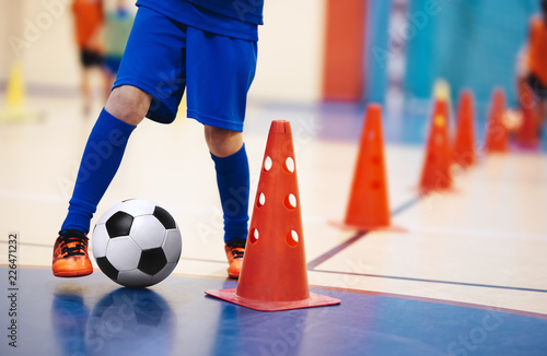 Indoor soccer players training with balls. Indoor soccer sports hall. Indoor football futsal player, ball, futsal floor and red cone. Futsal training dribbling drill. Sports background. Futsal league