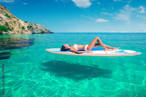 Foto op Canvas Ontspanning Young beautiful woman relaxing in the sea on a SUP board. The girl sunbathes on the beach of the island on vacation.