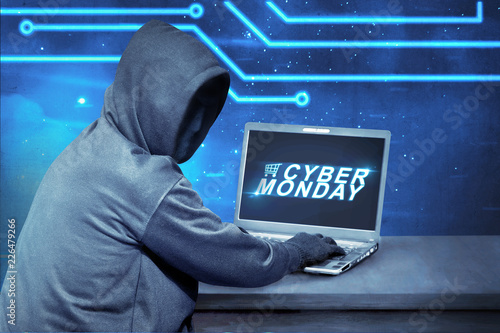 Hacker using laptop with text cyber monday on the screen