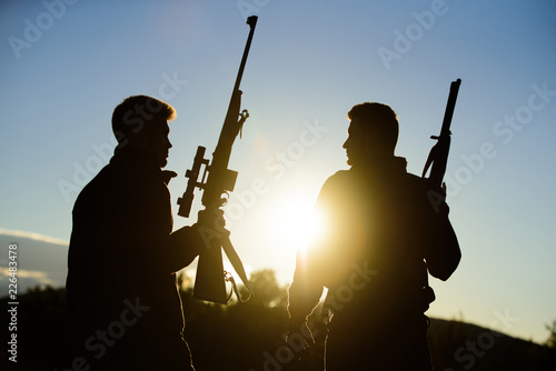 Foto op Canvas Jacht Hunter friend enjoy leisure. Hunters friends gamekeepers with guns silhouette sky background. Hunters rifles nature environment. Hunting with partner provide greater measure safety fun and rewarding