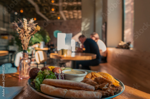 Fotografering  Blurred cafe interior with customers eating and dish of falafel and grilled chic
