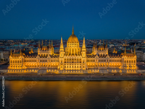 Budapest, Hungary - Aerial view of the beautiful illuminated Parliament of Hungary (Orszaghaz) at blue hour with clear blue sky