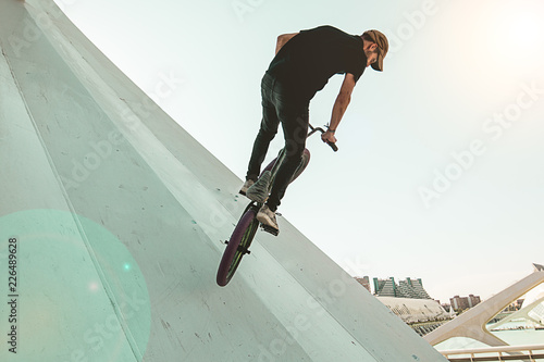 Young man with a bmx bike riding down the street