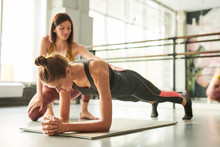 Full Length Portrait Of Contemporary Young  Woman Doing Plank Exercise During Fitnes Workout In Health Club With Female Instructor Helping Her, Copy Space