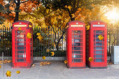 Fotografie, Obraz  Klassisch, rote Telefonzellen aufgereiht vor einem Park im Herbst in London