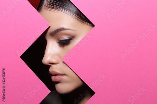 Fototapeta premium Twarz młoda piękna dziewczyna z jaskrawym makijażem patrzeje przez dziury w różowym papierze