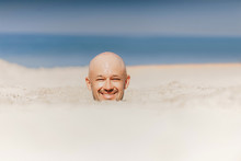 Male Bald Head Above Sand.  Man Buried  Alive In Desert. Happy Person Relaxing In Uninhabited Beach On Sun. Closeup Portrait Of Funny Guy Taking Sunbath With Body Under Ground Near Ocean. Therapy.