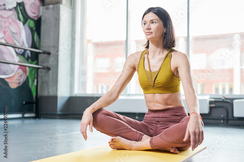 Full length portrait of contemporary young woman sitting in lotus position and looking away taking break frm yoga and listening to music, copy space