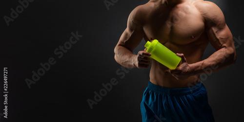 Fotografia  Bodybuilder after workout with a shaker on a dark background, banner