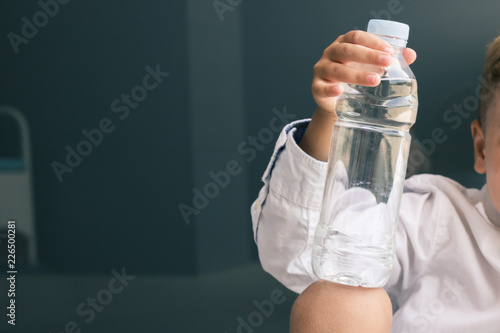 Foto  Close up of child holding bottle of water.