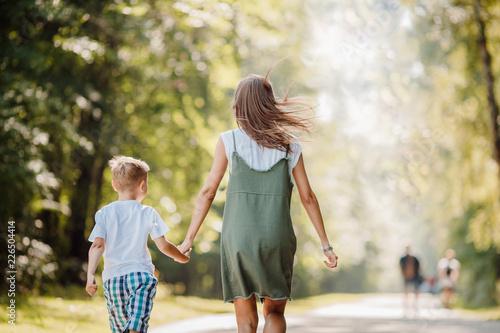 Carta da parati Sister teenager and little brother boy run their hands through park, sun light