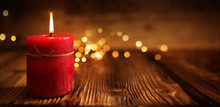 Burning Red Candle On Rustic Wood
