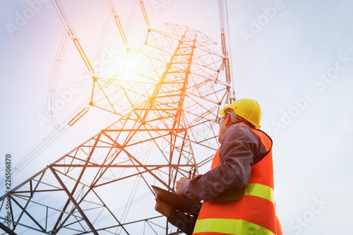 Fototapeta Engineering working on High-voltage tower, Check the information on paper. obraz