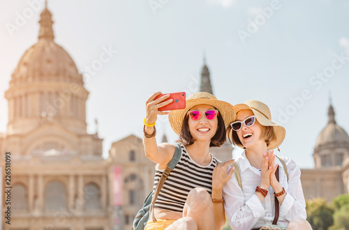 Foto  Two young happy women tourists friends hugging against the background of the Nat