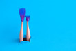 canvas print picture - Doll legs with snorkel fins on blue sea background minimal creative abstract concept.