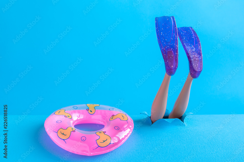 Fototapeta Close up of inflatable pool float and scuba diver feet with snorkel fins diving. Space for copy.