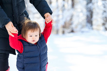 Toddler Boy Playing In The Snow With His Mother