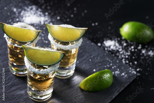 Golden tequila on black background Wallpaper Mural