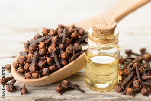 Fototapeta clove essential oil in the glass bottle, on the wooden board