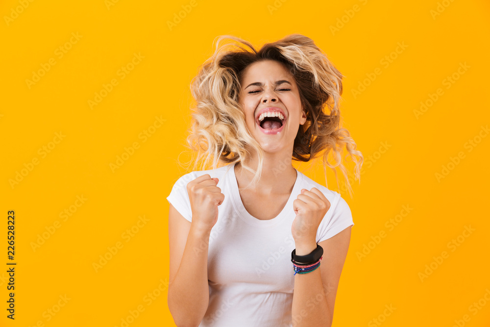 Fototapeta Photo of ecstatic woman in basic clothing screaming and clenching fists, isolated over yellow background