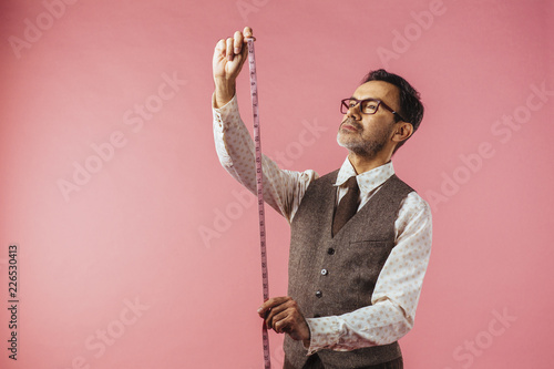 Obraz na plátně Horizontal portrait of a tailor holding fabric measure, isolated on pink studio