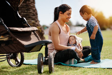 Mother Of Two Kids Sitting In Park In The Morning