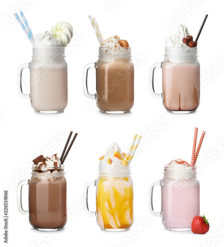Set with different delicious milk shakes in mason jars on white background
