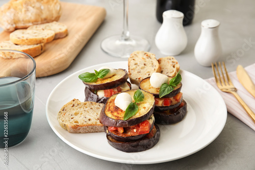 Baked eggplant with tomatoes, cheese and basil served on table