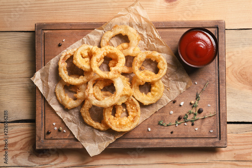 Homemade crunchy fried onion rings and sauce on wooden background, top view