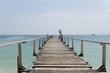 Langer Holzsteg über türkisfarbenem Meer in Thailand