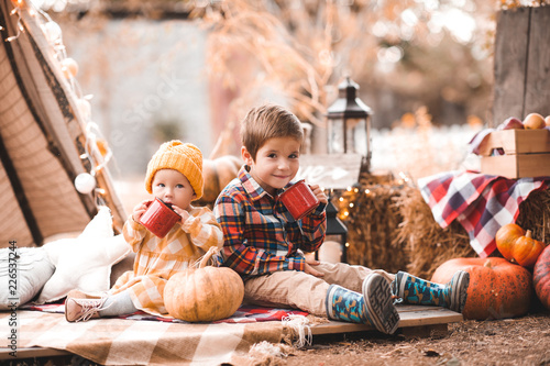 Cute Baby Girl With Kid Boy Drinking Hot Tea With Autumn Decor