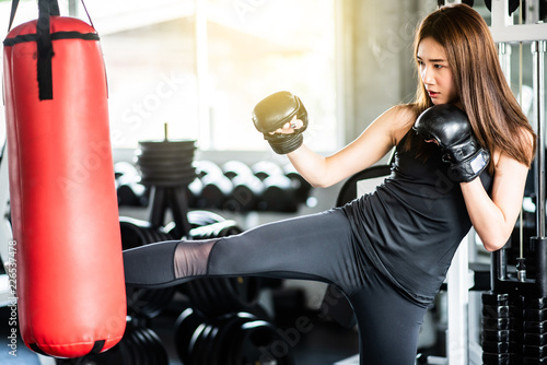 Fotografía Attractive female boxer training with kick boxing at gym with blackgloves