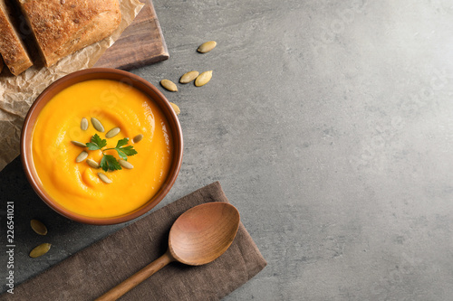 Flat lay composition with pumpkin cream soup in bowl on gray background. Space for text